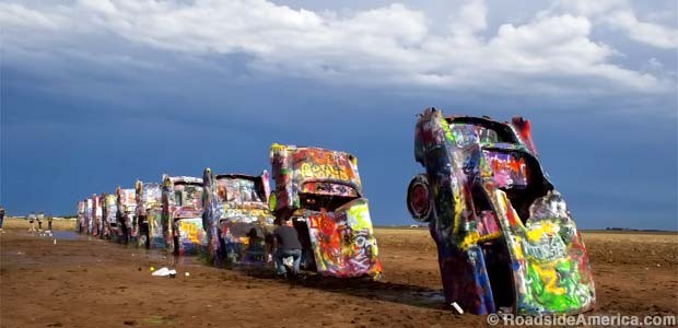 This is a public art installation and sculpture in Amarillo, Texas, USA. It was created in 1974 by Chip Lord, Hudson Marquez and Doug Michels, who were a part of the art group Ant Farm. It consists of what were (when originally installed during 1974) either older running used or junk automobiles, representing a number of evolutions of the car line from 1949 to 1963, half-buried nose-first in the ground, at an angle purportedly corresponding to that of the Great Pyramid of Giza in Egypt. Identify the brand of cars?