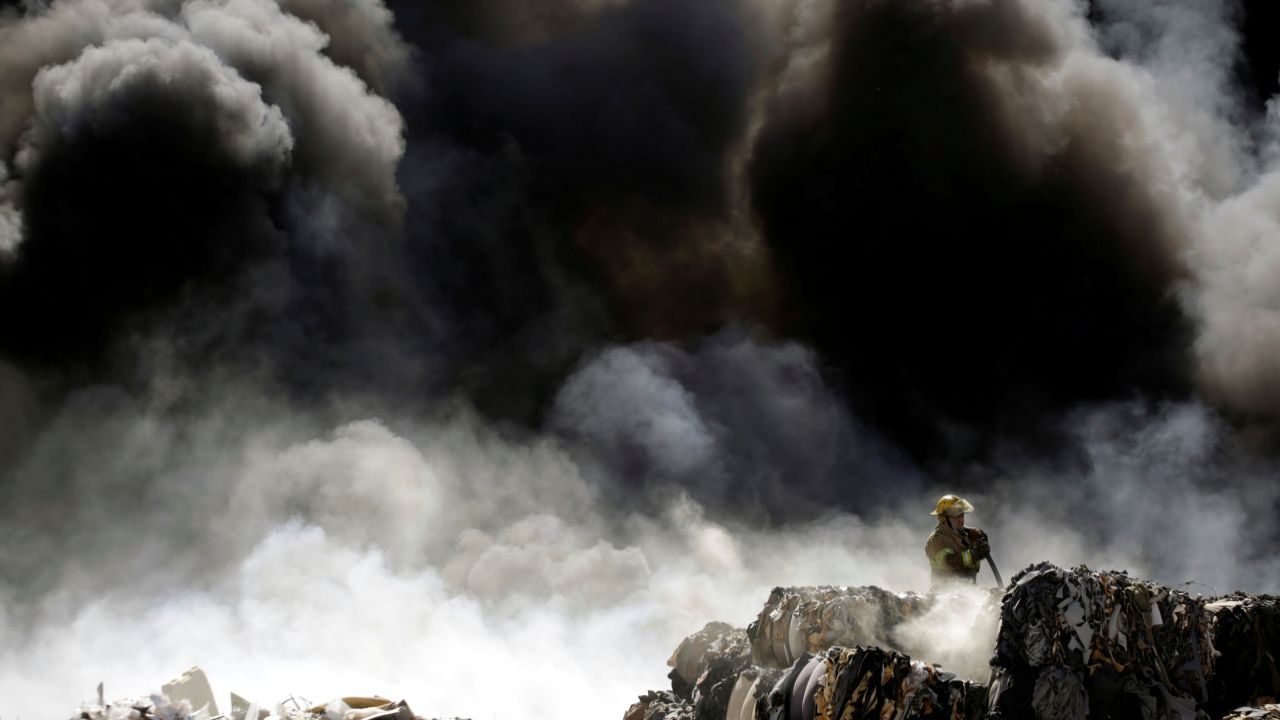 A firefighter works to extinguish the fire as it burns through a pile of old tyres at a recycling centre in Ciudad Juarez, Mexico. (Reuters)