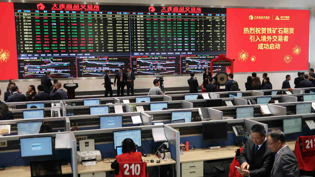 People attend a ceremony marking the opening of iron ore futures to foreign investors, at Dalian Commodity Exchange in Dalian, Liaoning province, China. (REUTERS)
