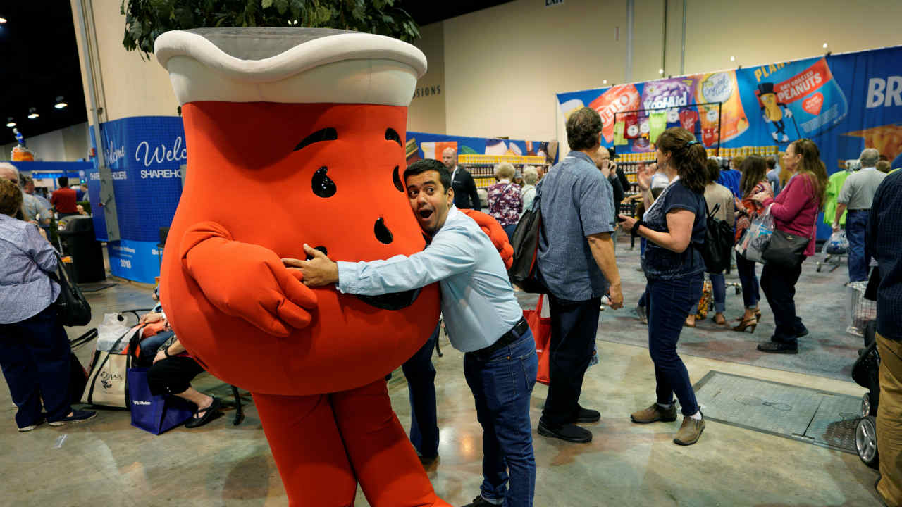 Scores of investors gather in Omaha, Nebraska to take part in the AGM. The company is known for investing in products that are household names in America. Pictured here is a sharedholder hugging a Mr. Kool-Aid characterin the exhibit hall this year. (REUTERS)