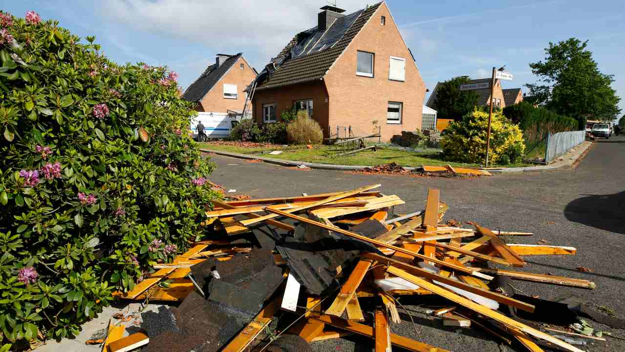 Debris sit on a street as workers repair a roof after a tornado last night hit the area of Boisheim, west of Duesseldorf, Germany. (Reuters)