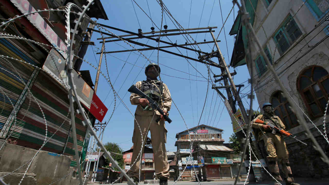 Indian policemen stand guard behind concertina wire during a strike called by separatists to mark the death anniversaries of chief cleric of Kashmir, Moulana Mohammad Farooq and Abdul Gani Lone, a Kashmiri separatist leader, in Srinagar. (REUTERS)