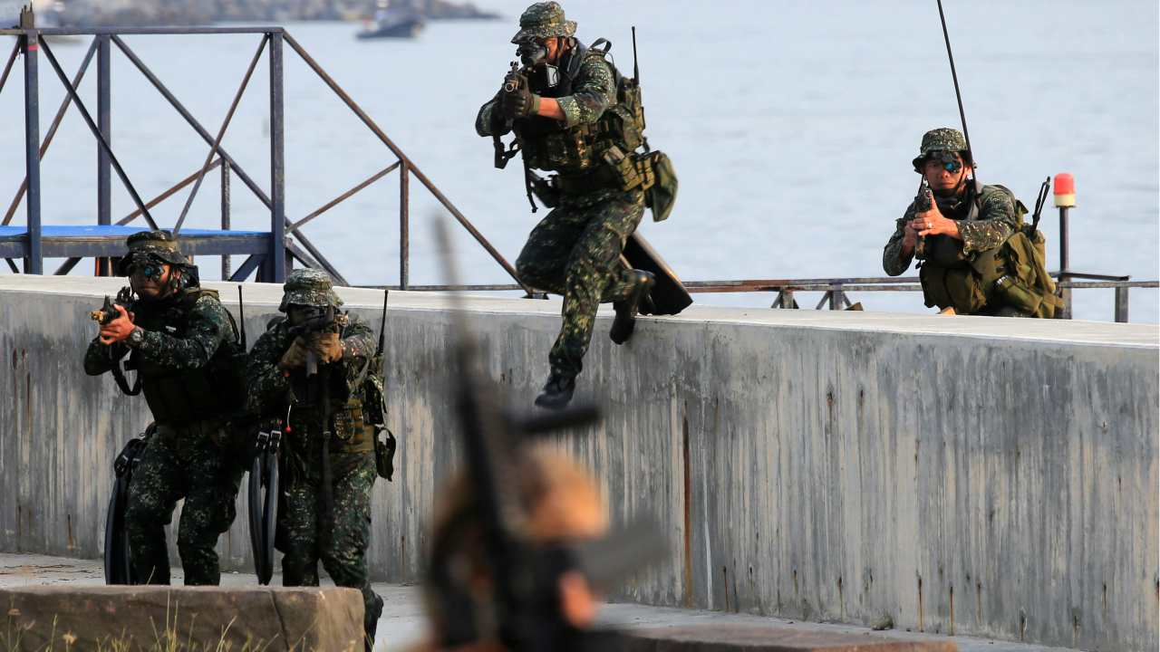 Members of the Marine Special Operations Group take up position to attack simulated rebels' camp as part of their capability demonstration during the Philippine Navy's 120th anniversary in Metro Manila, Philippines. (Reuters)