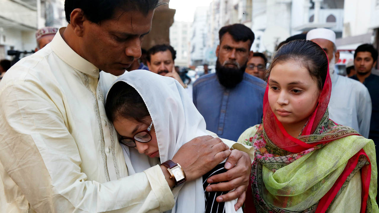 Aziz Sheikh (L) father of Sabika Aziz Sheikh, a Pakistani exchange student, who was killed with others when a gunman attacked Santa Fe High School in Santa Fe, Texas, U.S., comforts her friends, during a funeral in Karachi, Pakistan. (Reuters)