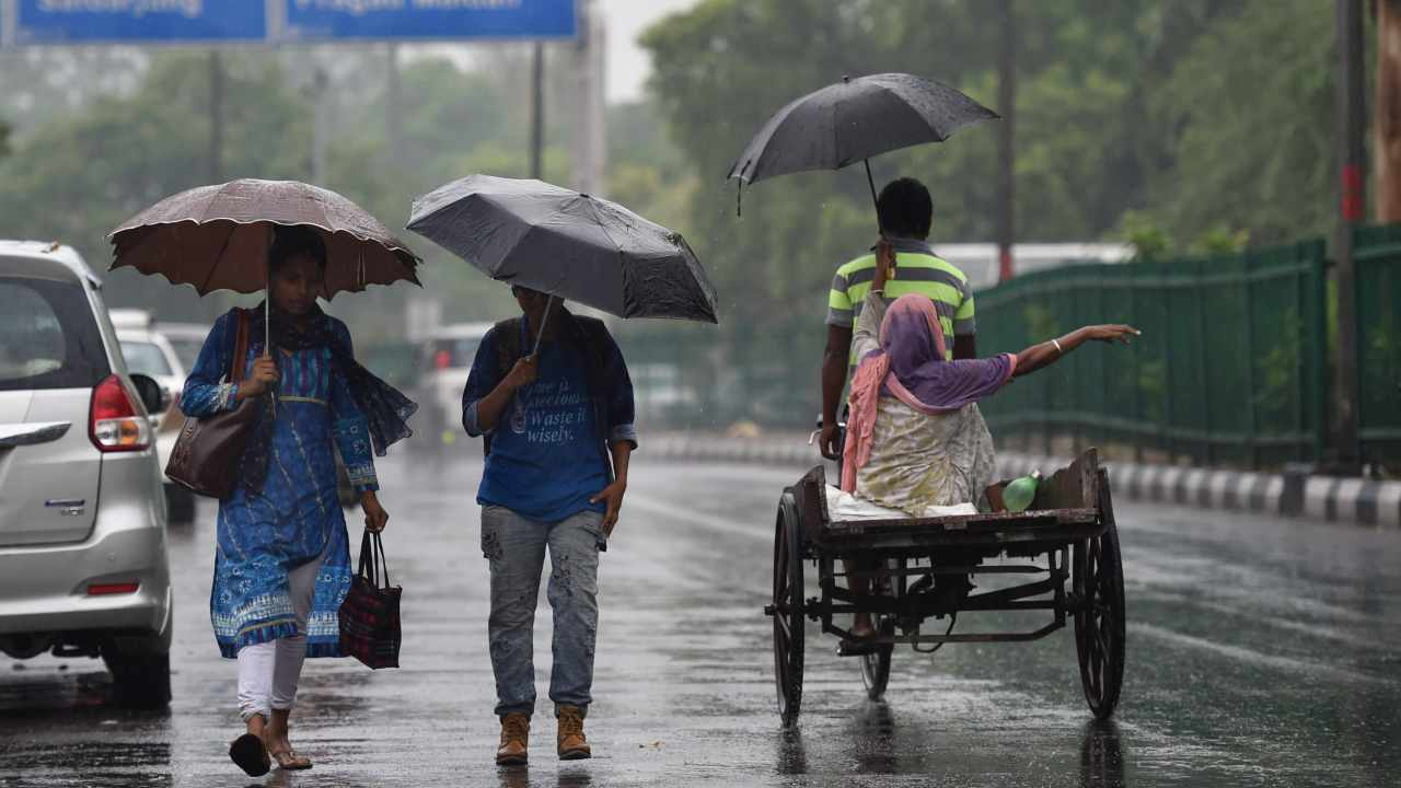 Commuters cross a road during a rainfall in New Delhi. (PTI)