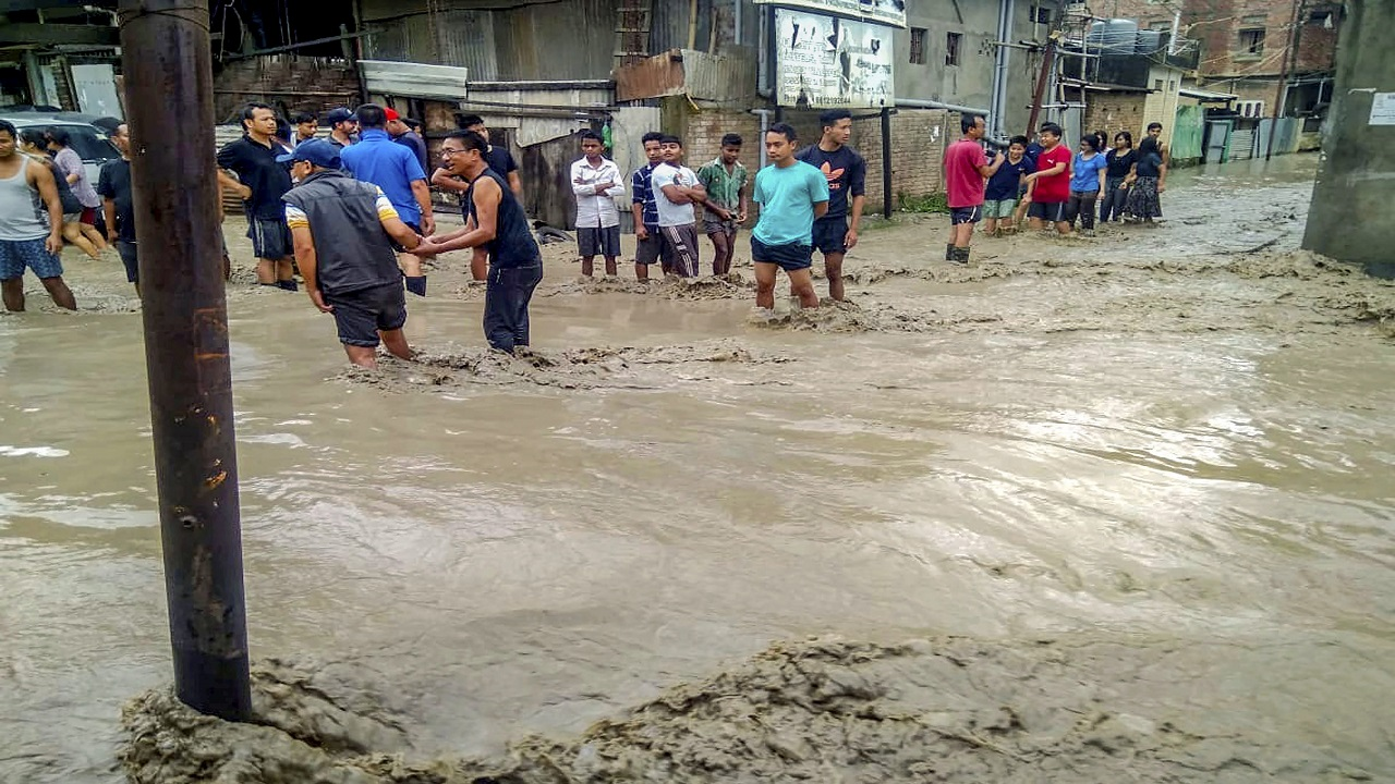 People walk through the flood waters after heavy rains, in Imphal. (Image: PTI)