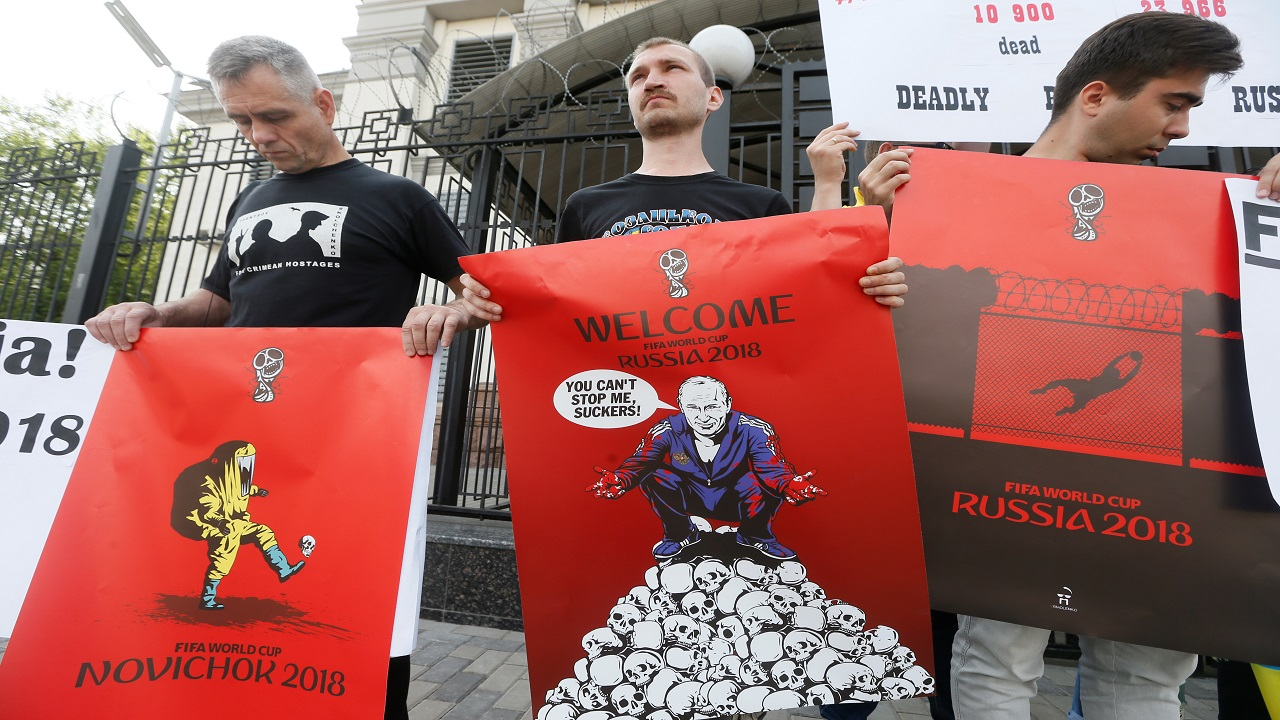 Participants hold posters by artist Andrii Yermolenko during a rally demanding the boycott of the 2018 FIFA World Cup and the release of political prisoners held in Russia, in front of the Russian embassy in Kiev, Ukraine (Image:Reuters)