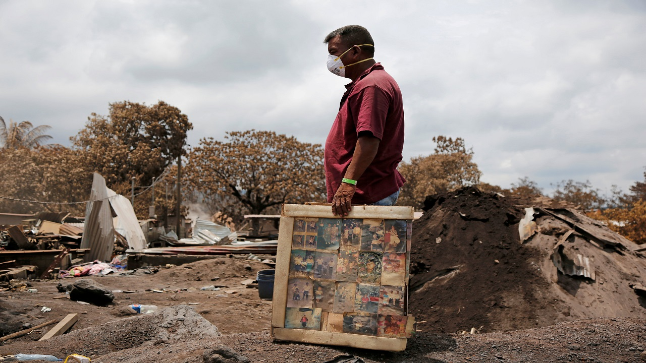 A resident holds framed pictures of his family, recovered from his house in an area affected by the eruption of the Fuego volcano, in San Miguel Los Lotes, in Escuintla, Guatemala. (Image:Reuters)