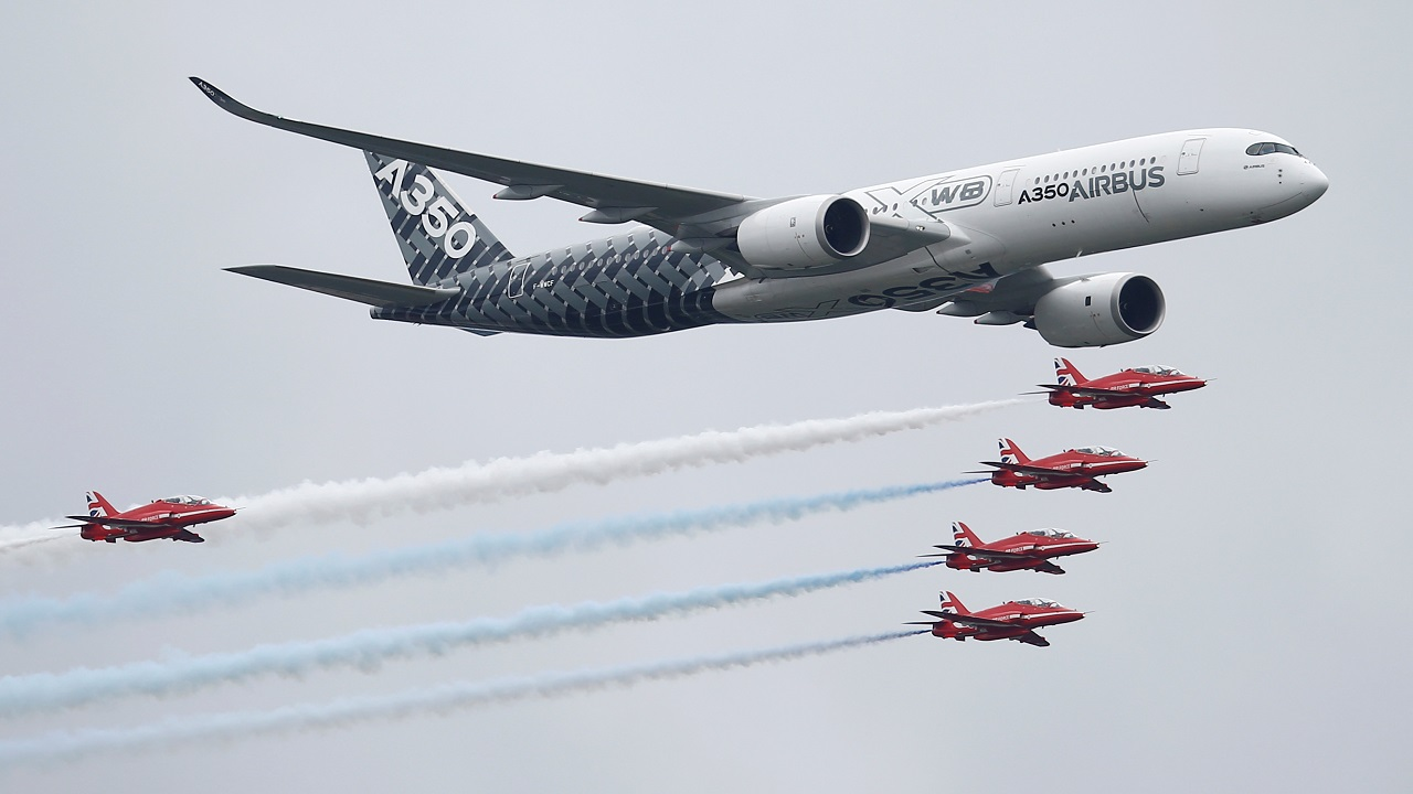An Airbus A350 aircraft flies in formation with Britain's Red Arrows flying display team at the Farnborough International Airshow in Farnborough, Britain. (Image: Reuters)