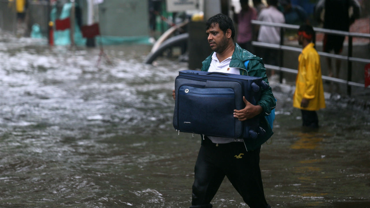 A man carries his suitcase as he walks through a water-logged street after heavy rains. (Image: Reuters)