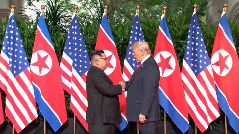 US President Donald Trump and North Korean leader Kim Jong Un shake hands ahead of their meeting at Capella Hotel in Singapore, Tuesday. (AP)