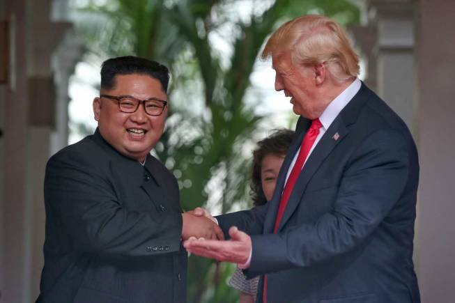US President Donald Trump shakes hands with North Korea leader Kim Jong Un at the Capella resort on Sentosa Island Tuesday. (AP)