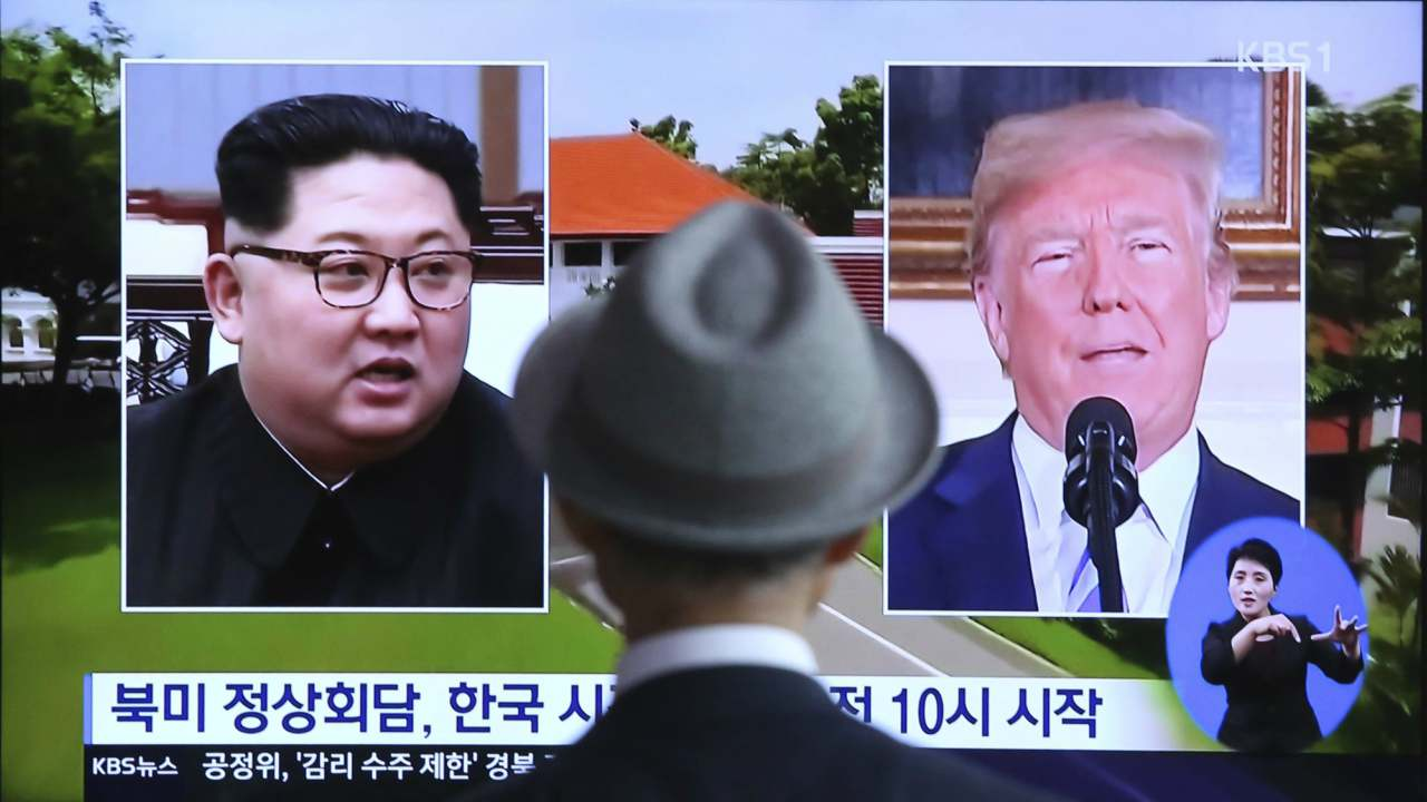 """A  man watches a TV screen showing file footage of U.S. President Donald Trump, right, and North Korean leader Kim Jong Un during a news program at the Seoul Railway Station in Seoul, South Korea8.  Final preparations are underway in Singapore for Tuesday's historic summit between President Trump and North Korean leader Kim, including a plan for the leaders to kick things off by meeting with only their translators present, a US official said.  The signs read: """" Summit between the United States and North Korea."""" (AP/PTI)"""