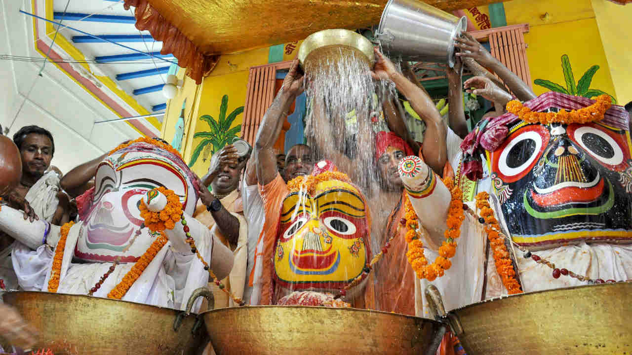 Hindu priests pour milk over a statue of Lord Jagannath during the Jal Yatra procession inside a temple, in Agartala, Tripura. (Image: PTI)
