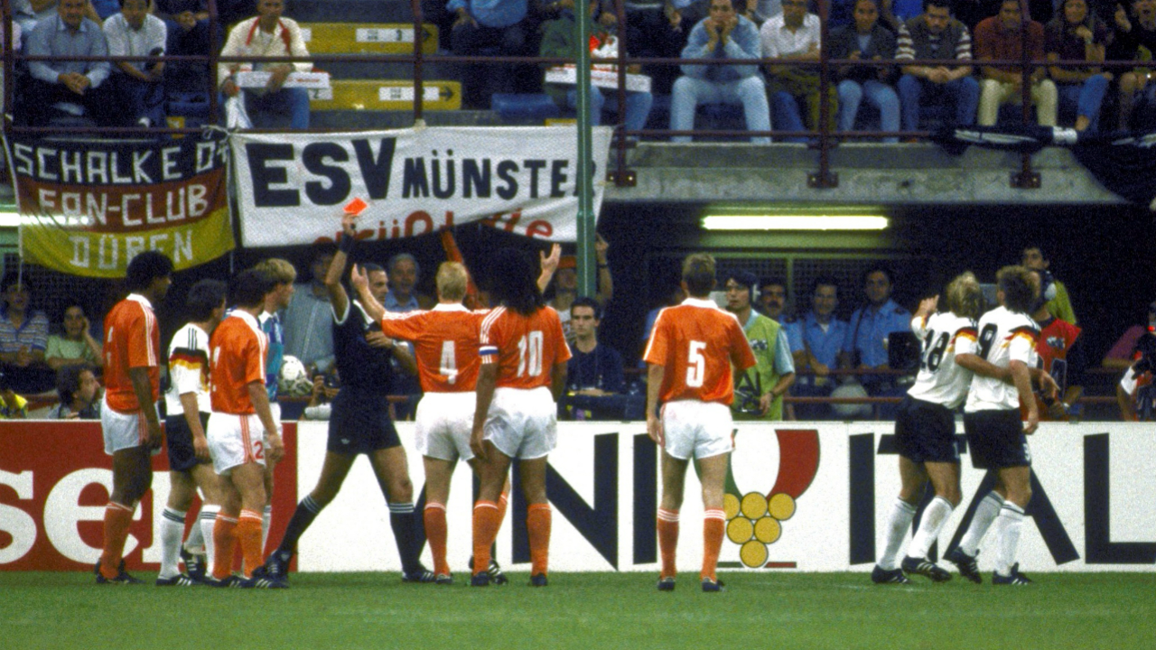 Rijkaard spits on Voellar (Italy 1990) | After picking up a booking that would ensure he missed the quarter-finals, an infuriated Frank Rijkaard spat at German striker Rudi Voellar's hair as he made his way back to defend the resulting free-kick. A disgusted Voellar then got into a verbal exchange with Rijkaard and was subsequently booked too. After the free-kick, Voellar clattered into the Dutch keeper and Rijkaard tried to pull him to his feet by his ear before stamping on his boot. Voellar went down and the referee, who had enough by this point, showed a red card to Rijkaard before dismissing an incredulous Voellar too.