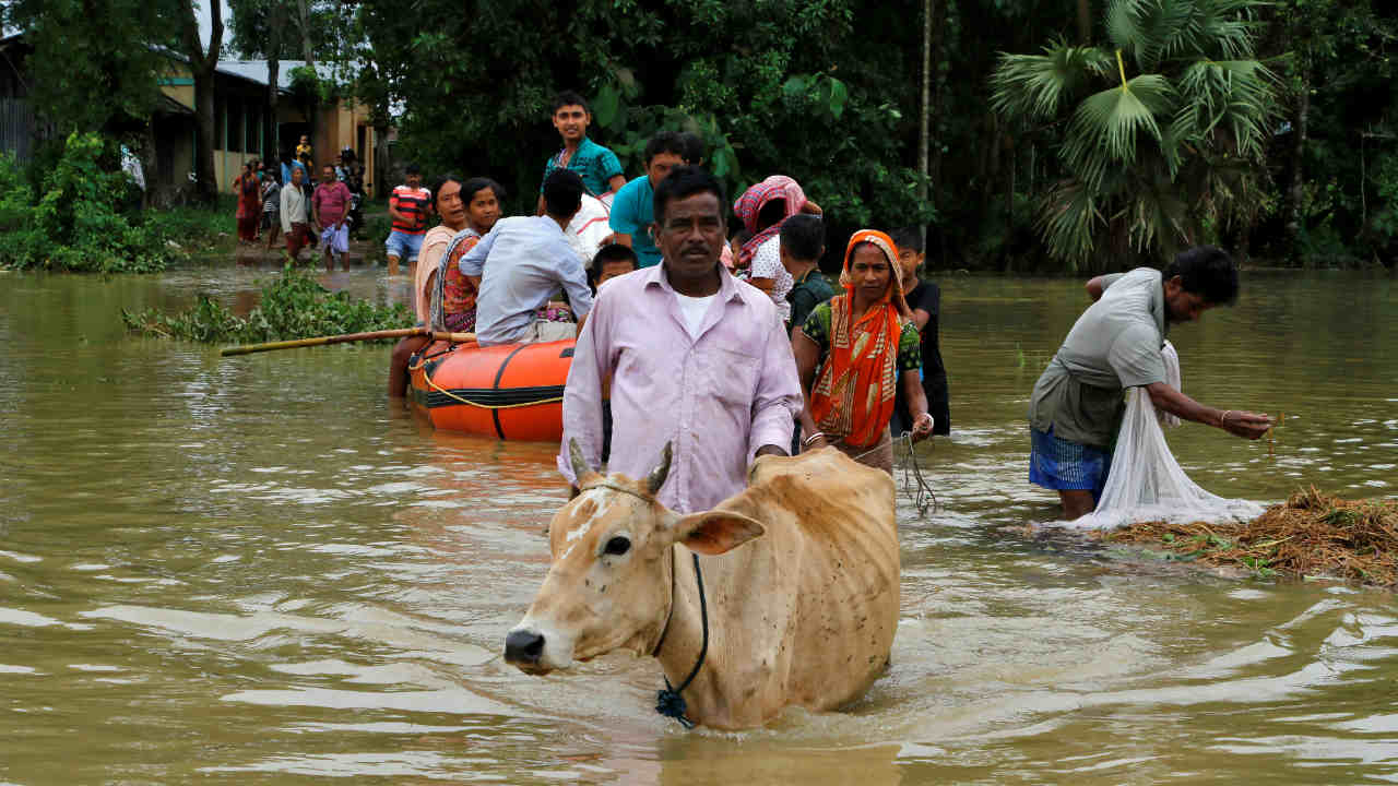 People wade through a flooded area after heavy rains at Mogpara village, south of Agartala, India, June 13, 2018. (Image: Reuters)