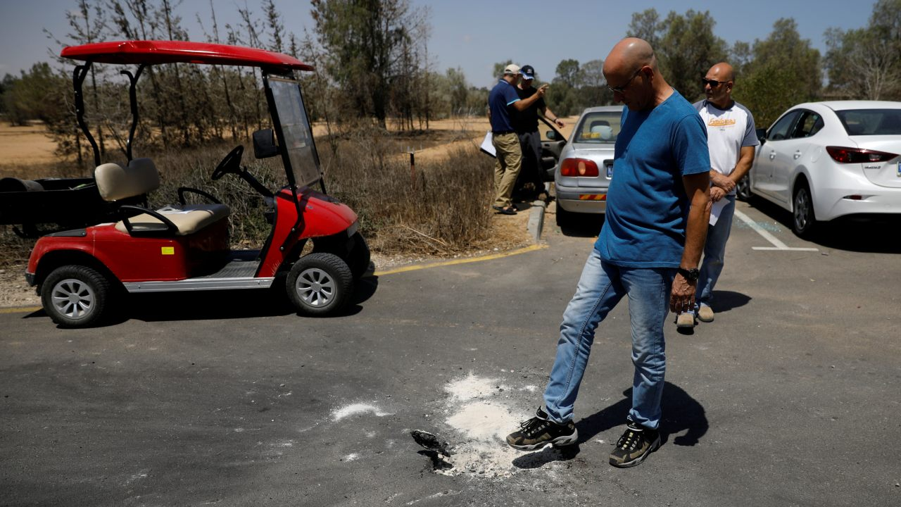 A man stands next to a crater on a road, caused by a rocket fired from the Gaza Strip that landed near it, in a Kibbutz on the Israeli side of the Israeli-Gaza border. (Image: Reuters)