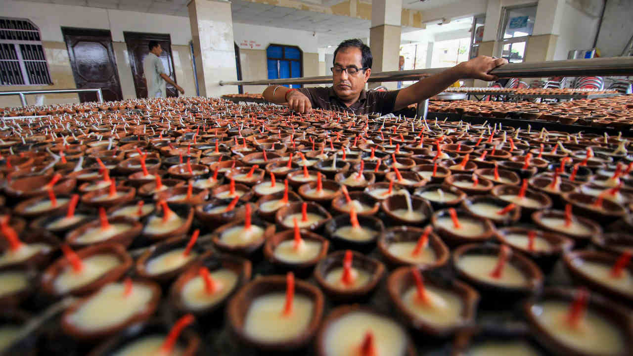 A person from the Kashmiri Pandit community arranges traditional earthern lamps at the replica of Kheer Bhawani temple, during preparations for 'Jyeshthaashtami' annual congregation in Jammu. (Image: PTI)