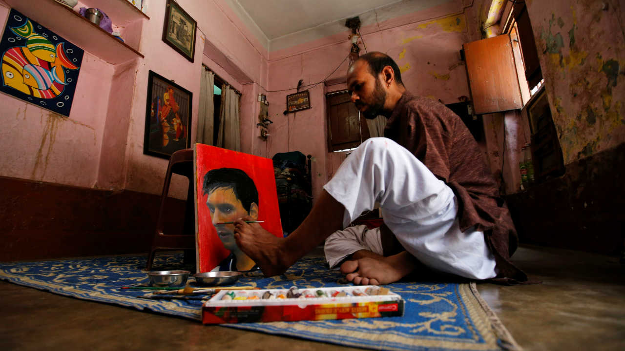 Ranjan Kurmi, 32, a fan of Argentina's football team paints footballer Lionel Messi's image on a canvas ahead of FIFA World Cup 2018 Group D match between Argentina and Iceland, inside a house on the outskirts of Kolkata. (Image: Reuters)