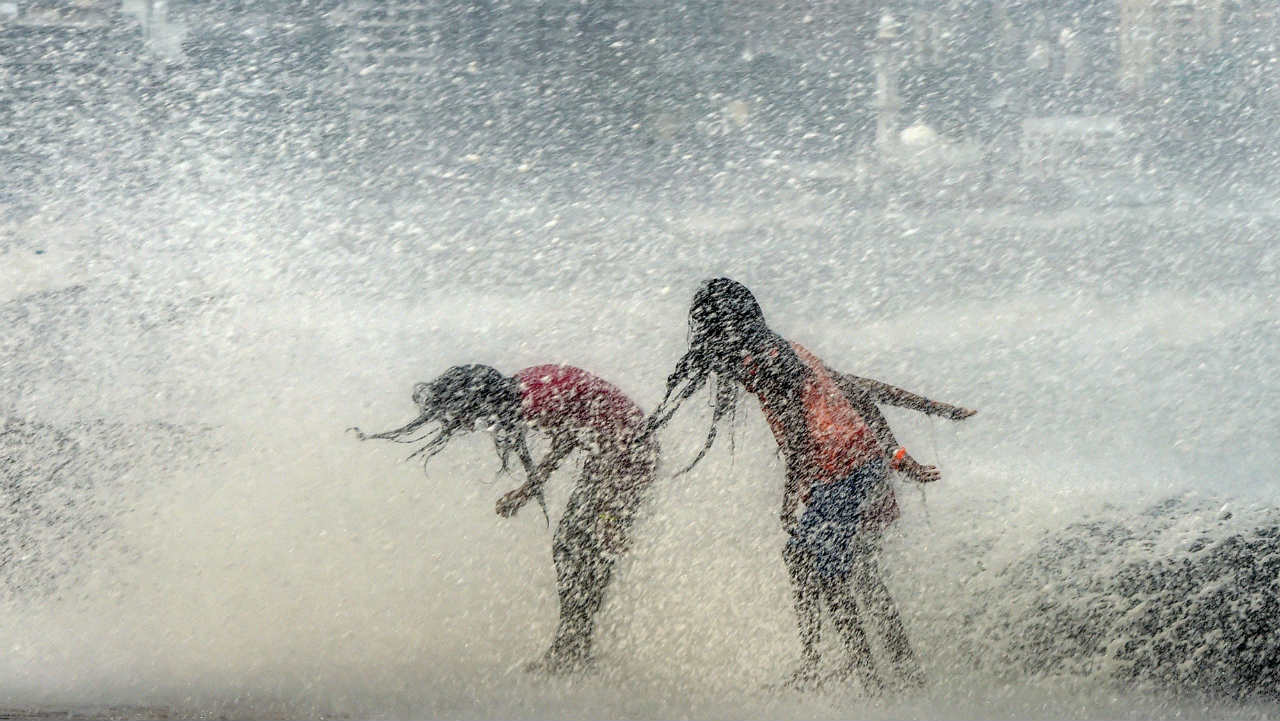 Children play during a high tide at the Worli Seaface in Mumbai. (Photo: PTI)
