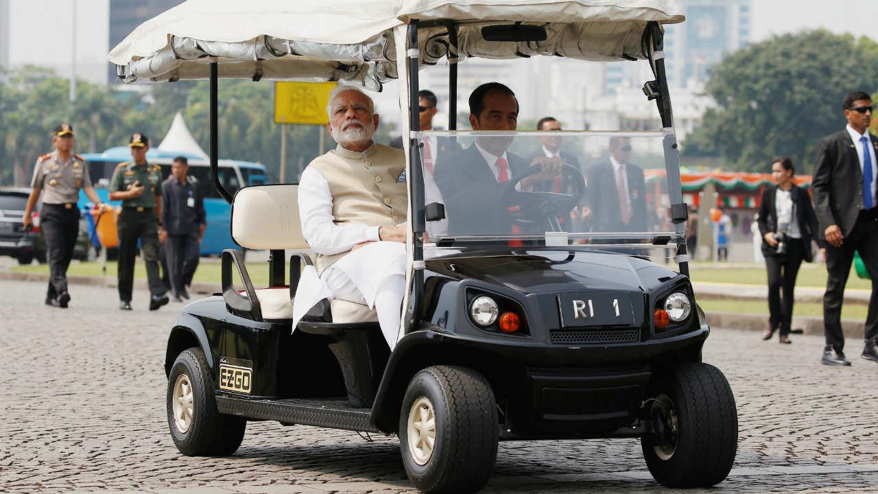 Narendra Modi sits as Joko Widodo drives golf cart at National Monument in Jakarta. (Photo: Reuters)