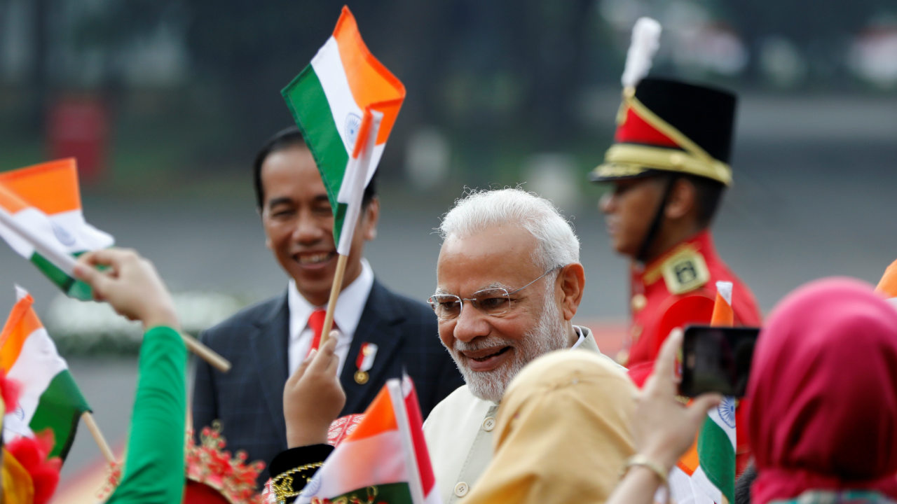 Narendra Modi is greeted by the children in traditional costumes as Indonesia President Joko Widodo looks on. (Photo: Reuters)