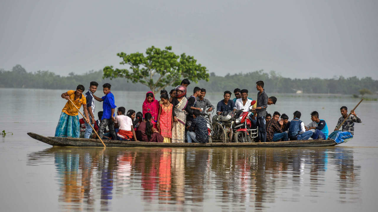 Villagers cross a flood-affected area on a boat, in Hojai. (PTI)