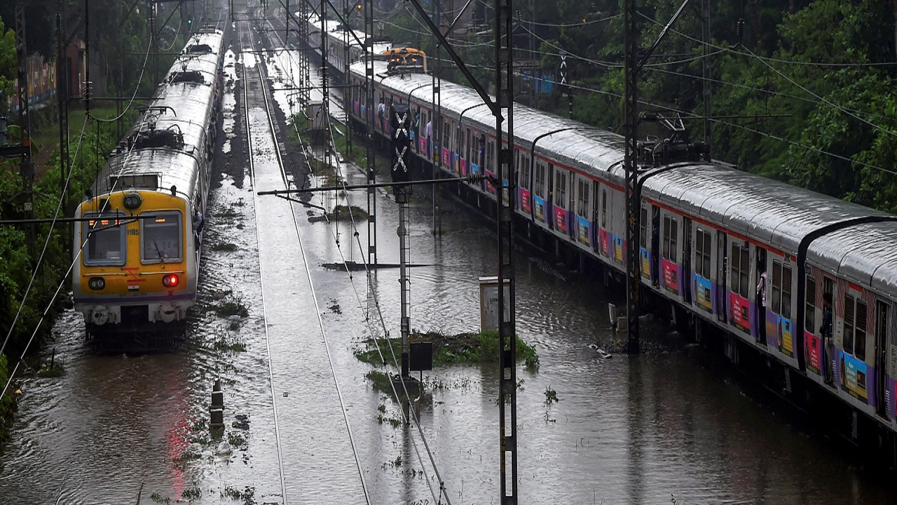 A train chugs on water-logged tracks during heavy rains, in Mumbai. Several trains were delayed along the harbour and central lines. (Image: PTI)