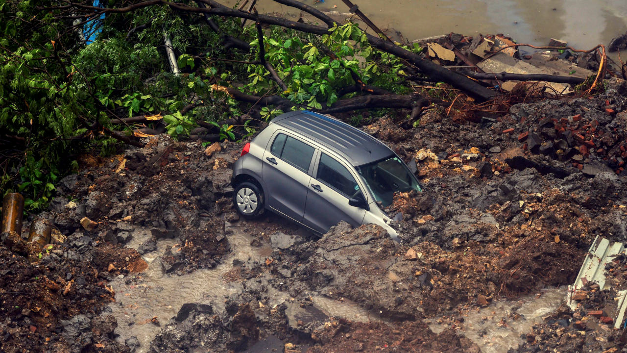 A car struck in debris after a wall collapsed at a construction site in Antop Hill, Wadala East area in Mumbai. (Image: PTI)