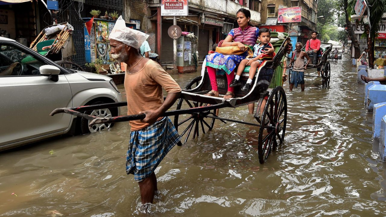A hand rickshaw puller carries his passengers across a water-logged street in Kolkata. (Image: PTI)