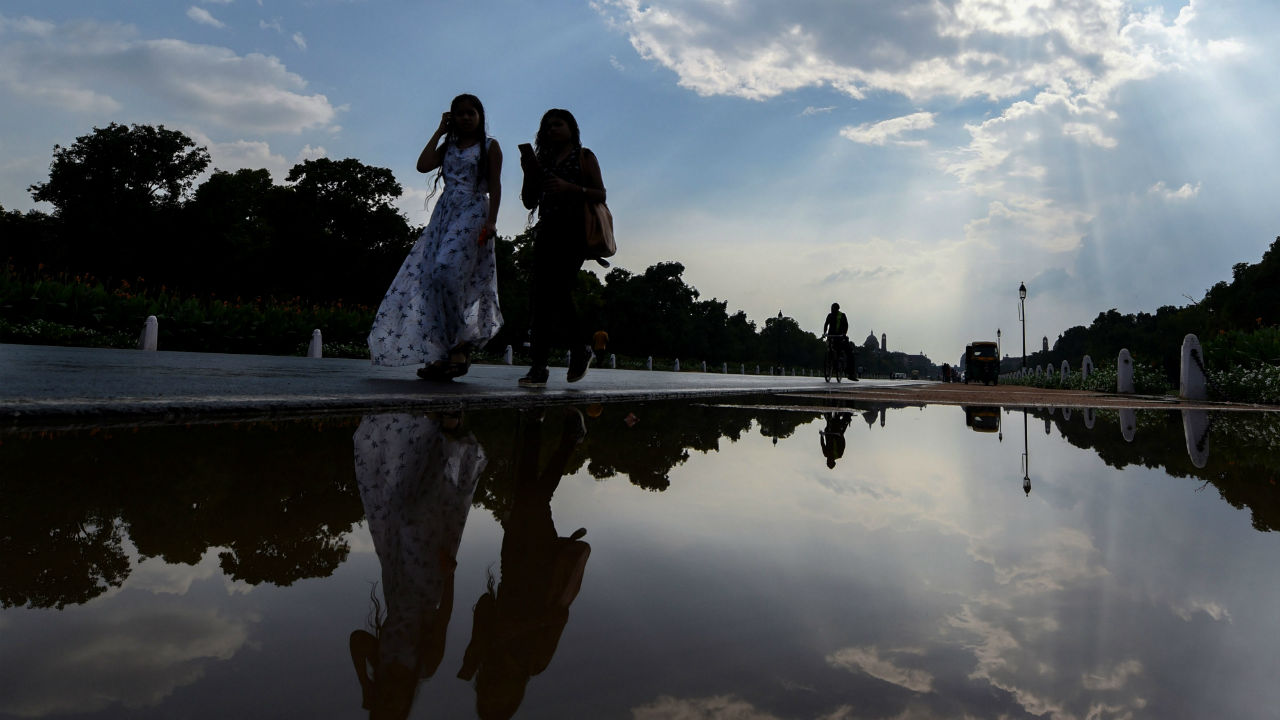 Women walk past a puddle of water at Rajpath after a short spell of rain, in New Delhi. (PTI)