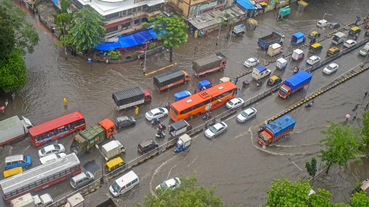Vehicles wade through water-logged street at King Circle after heavy rains in Mumbai. (Image: PTI)