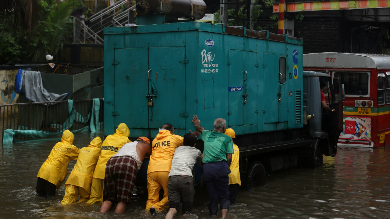 Police personnel and volunteers push a generator truck through a water-logged street after heavy rains. (Image: Reuters)