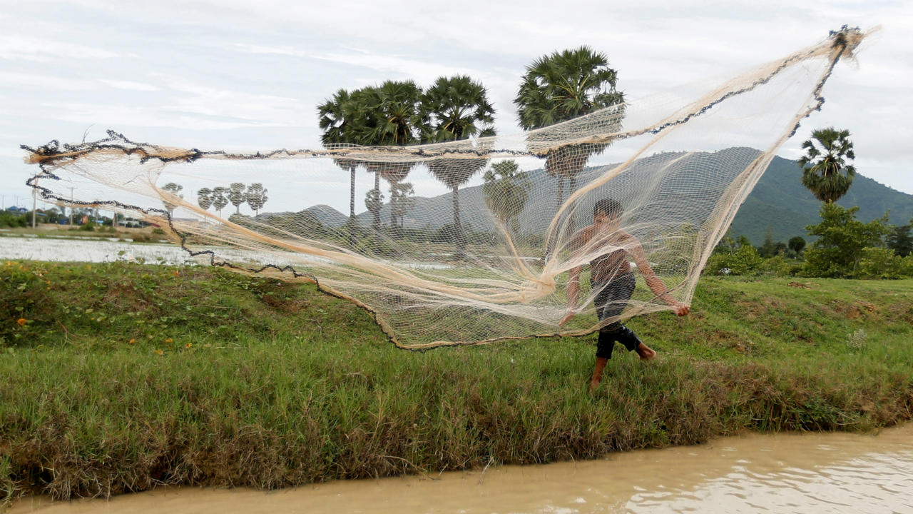 A man throws a fishing net into a canal in Kampong Speu province, Cambodia. (Image: Reuters)