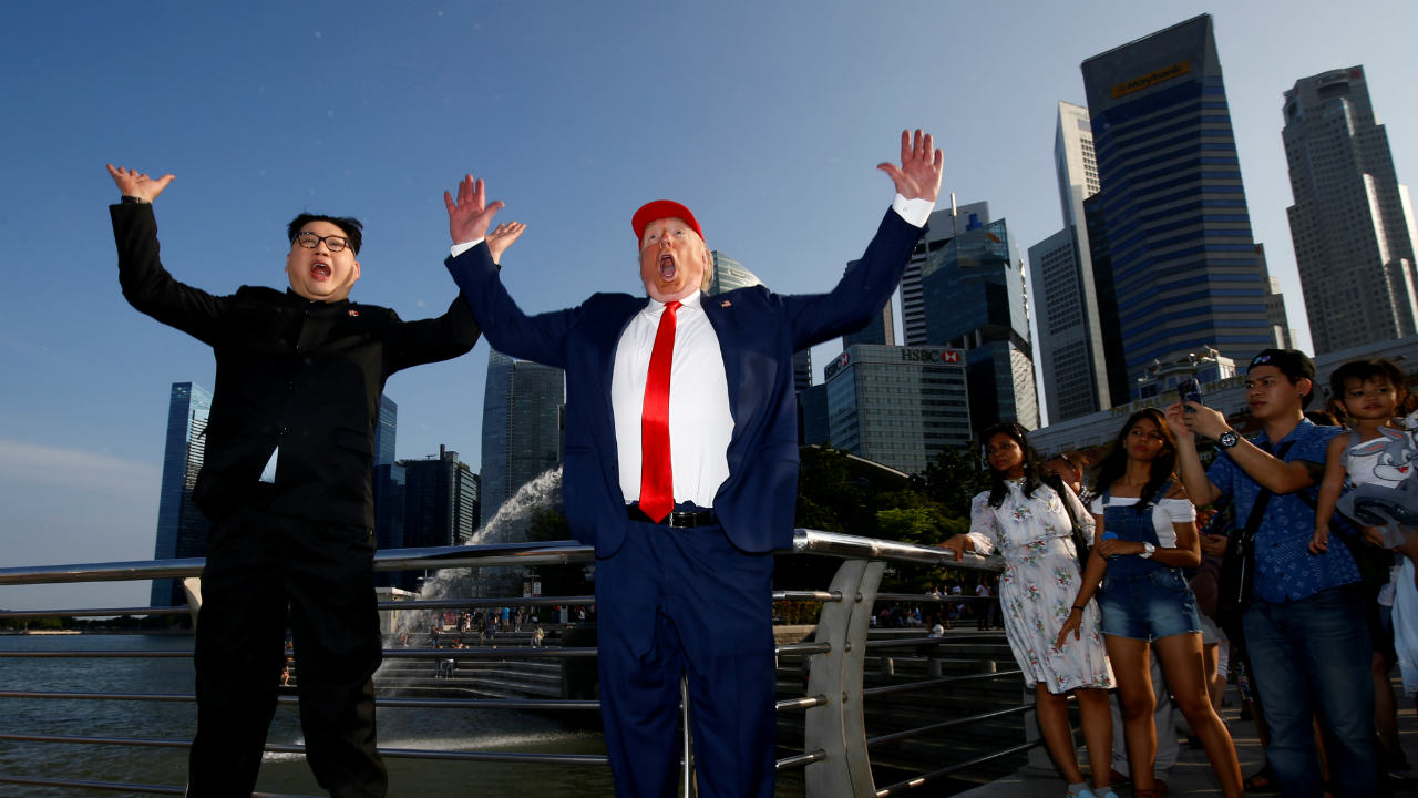 Howard, an Australian-Chinese impersonating North Korean leader Kim Jong-un, and Dennis Alan, impersonating US President Donald Trump, meet at Merlion Park in Singapore. (Image: Reuters)