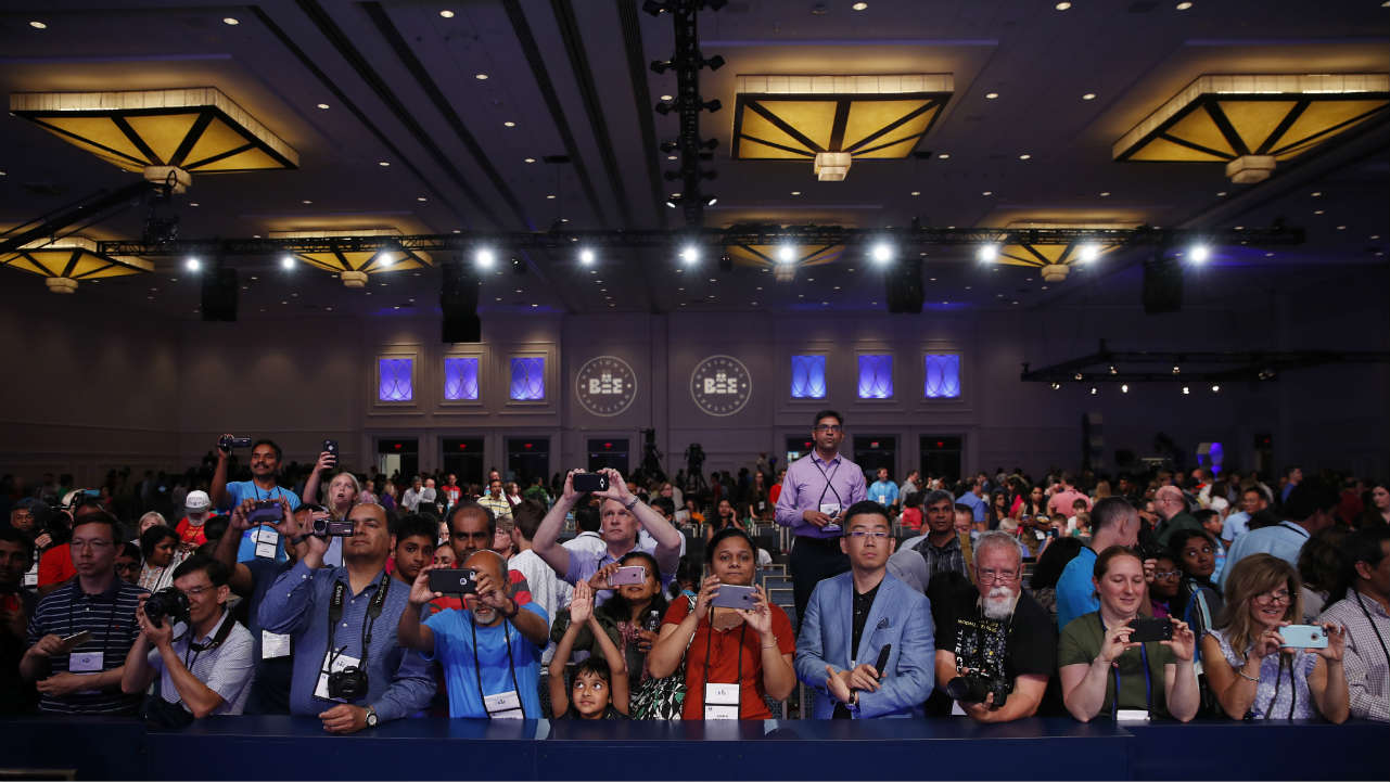 Parents and supporters gather in front of the stage to click snaps of the medal winners advancing to the final round. The 91st edition of the US annual spelling bee was held in Oxon Hill, Maryland. (Photo: AP)
