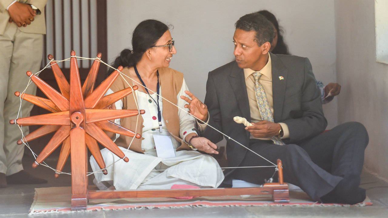 Seychelles President Danny Faure tries his hand on a spinning wheel or charkha', at Gandhi Ashram in Ahmadabad. Danny Faure is on a six-day visit to India. (Photo: PTI)