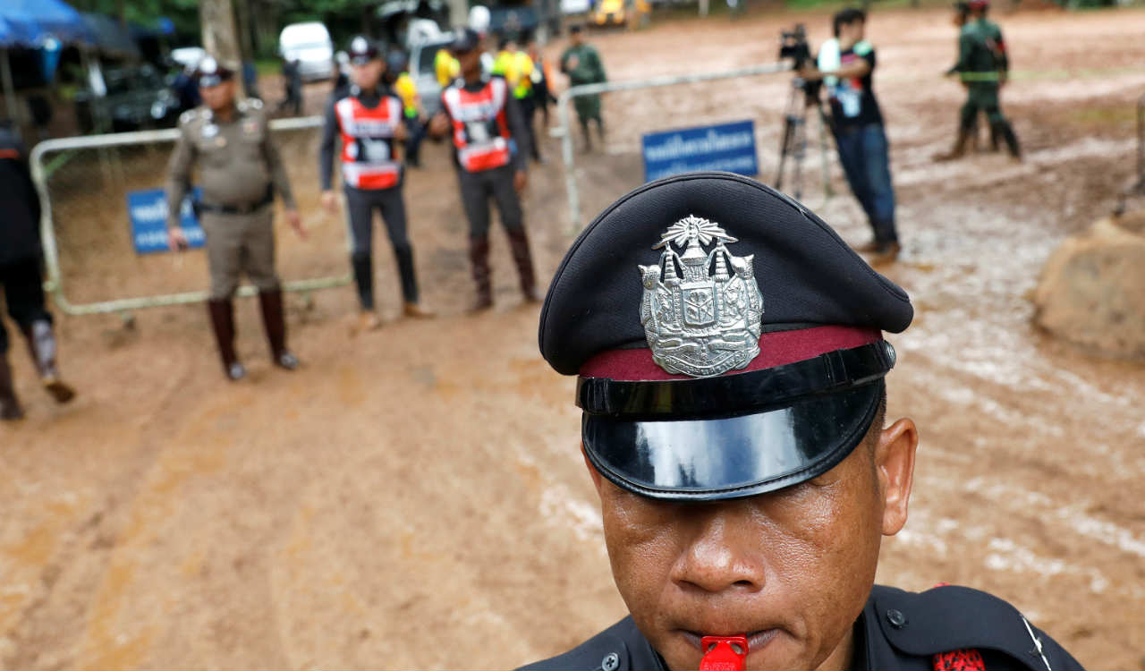 Police officers are seen near the Tham Luang cave complex, as a search for members of an under-16 soccer team and their coach continues, in the northern province of Chiang Rai, Thailand. (Image: Reuters)