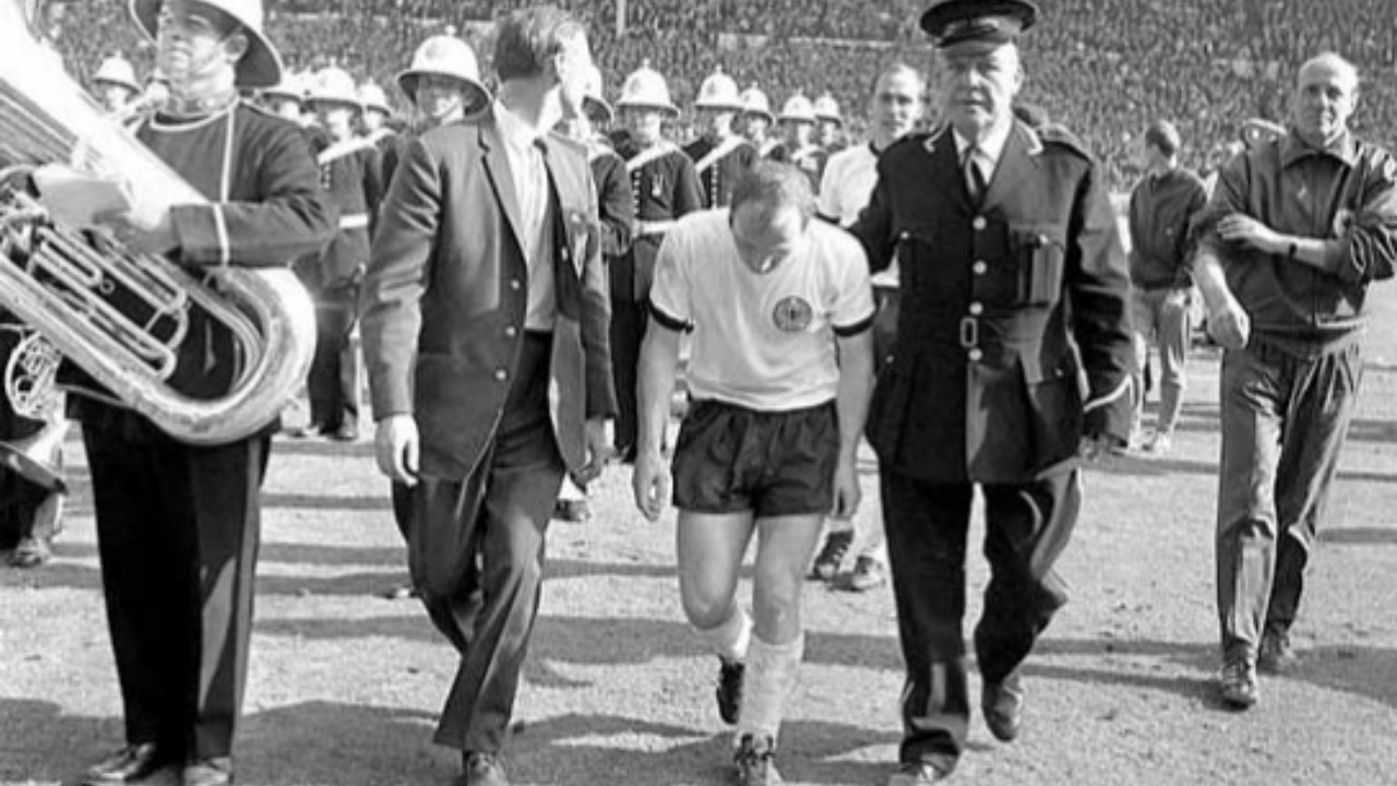 Q.5) This image of the West German captain trudging from the field at the end of the 4-2 loss to hosts England is considered a symbol of defeat after a great fight in Germany. In 1997, a German magazine noted that the image must have been taken at half-time due to the presence of the marching band. ______ gave credence to the theory, saying his head may have been bowed simply because he was checking his shoelaces. Further research, though, showed that theory to be unfounded: the marching band had appeared at full-time and the long shadows demonstrate that this image was taken later in the day. Name the player.