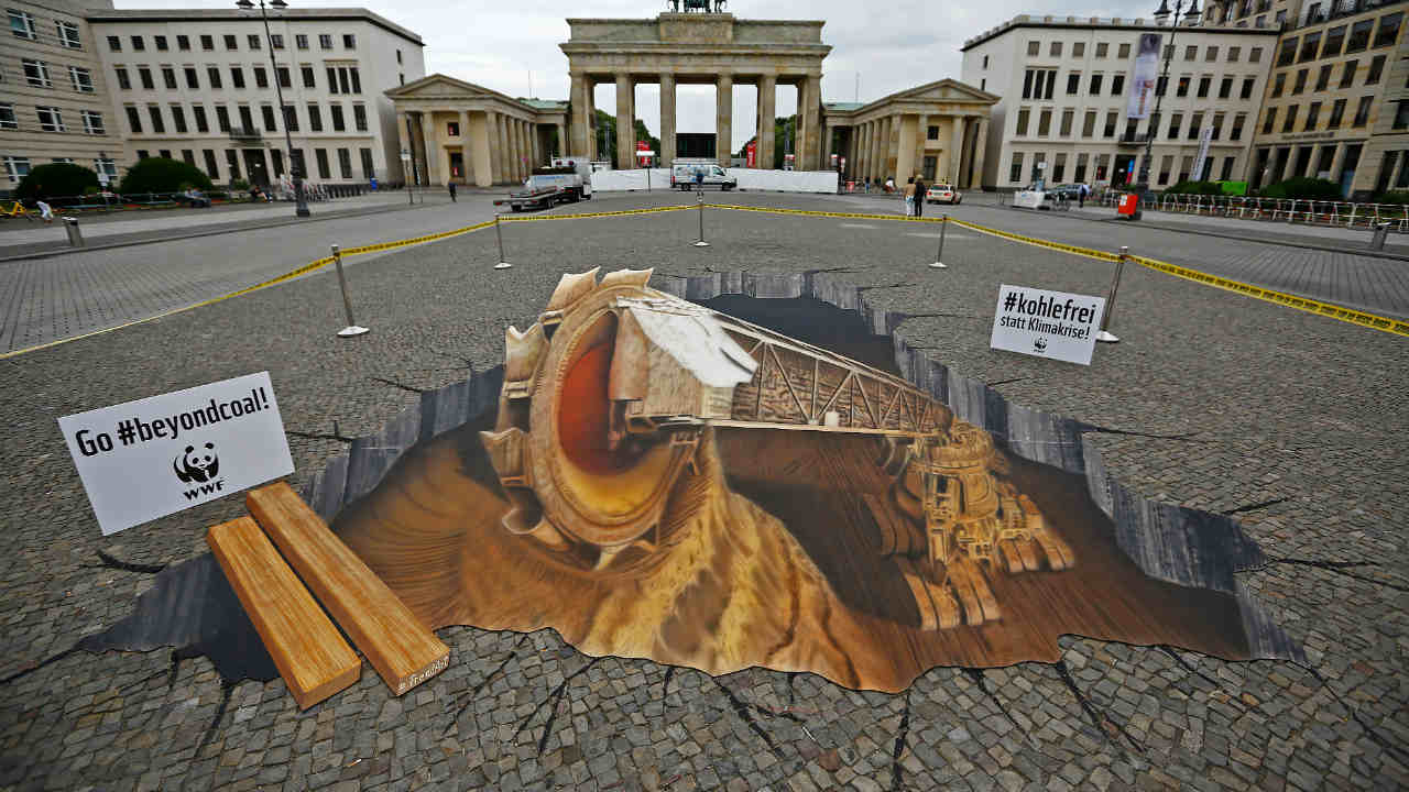 World Wide Fund For Nature (WWF) activists install a painting of a bucket wheel excavator in front of Brandenburg gate to protest against open cast mining in Berlin, Germany. (Image: Reuters)