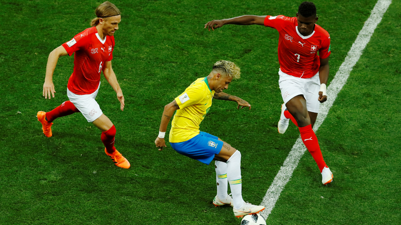 Neymar keeps the ball in play as Switzerland's Lang and Embolo try to close him down.