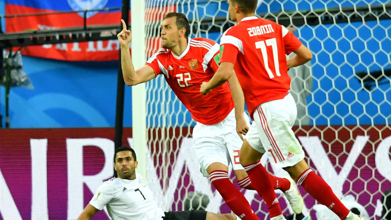 Egypt's Ahmed Fathi looks dejected after scoring Russia's first with an own goal while Russia's Artem Dzyuba and Roman Zobnin celebrate.