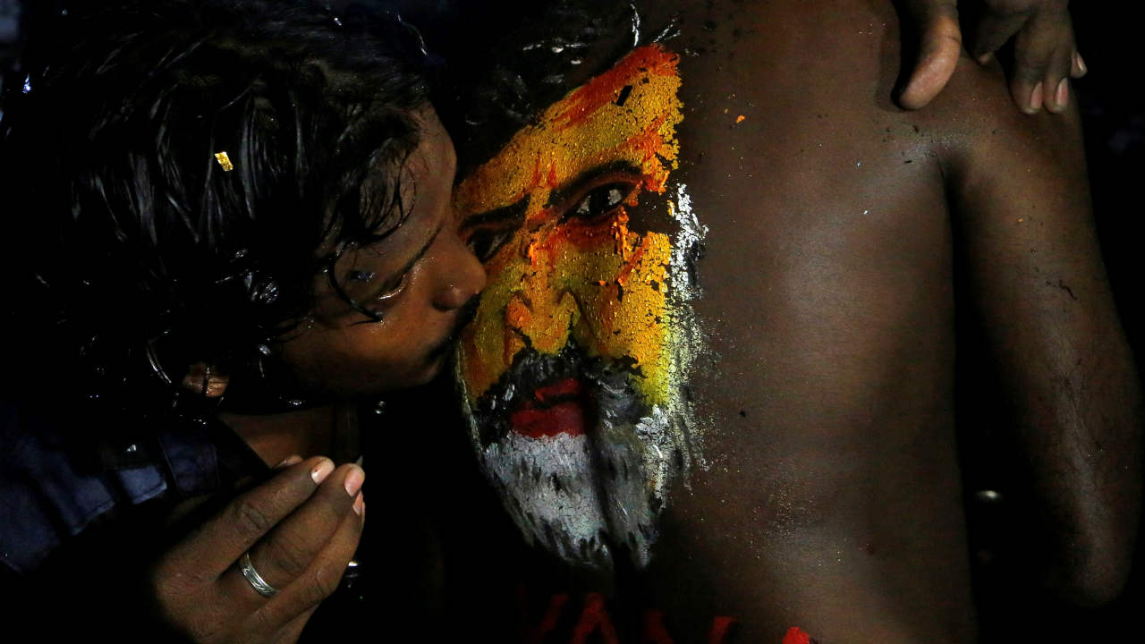 "A fan kisses an image of actor Rajinikanth painted on the body of another as they celebrate the release of his new movie ""Kaala"" in Mumbai. (REUTERS)"