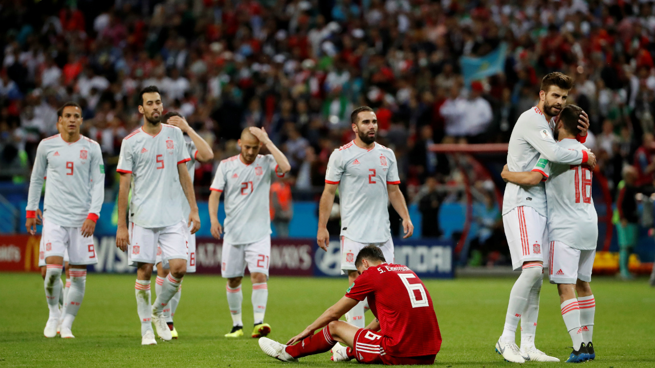 Spain's Gerard Pique and Jordi Alba celebrate victory as Iran's Saeid Ezatolahi looks dejected after the match.
