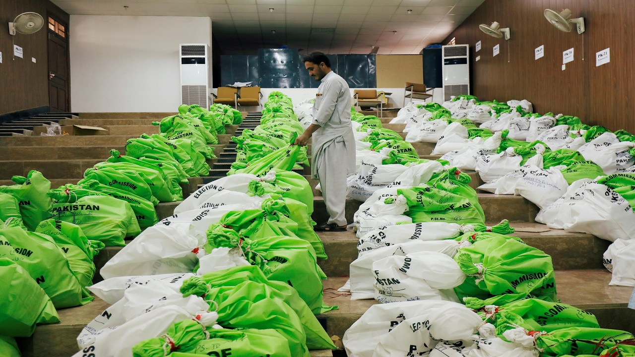 A worker arranges sacks of election materials for distribution among electoral workers, at a distribution point, ahead of general election in Peshawar, Pakistan. (Image: Reuters)