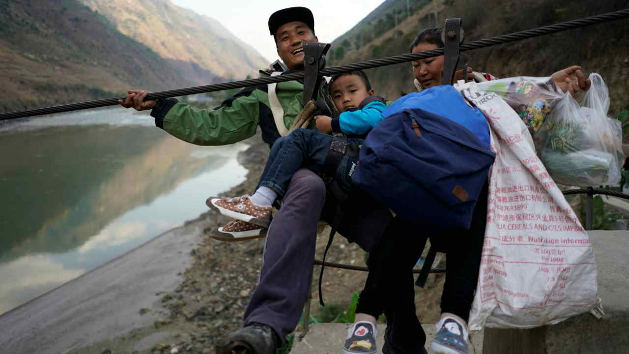 A family is ready to zip their way back to Lazimi village after shopping at the Saturday market. People estimate about 20 to 30 hamlets in the region still rely on the ziplines as their primary means across the river. (Reuters)