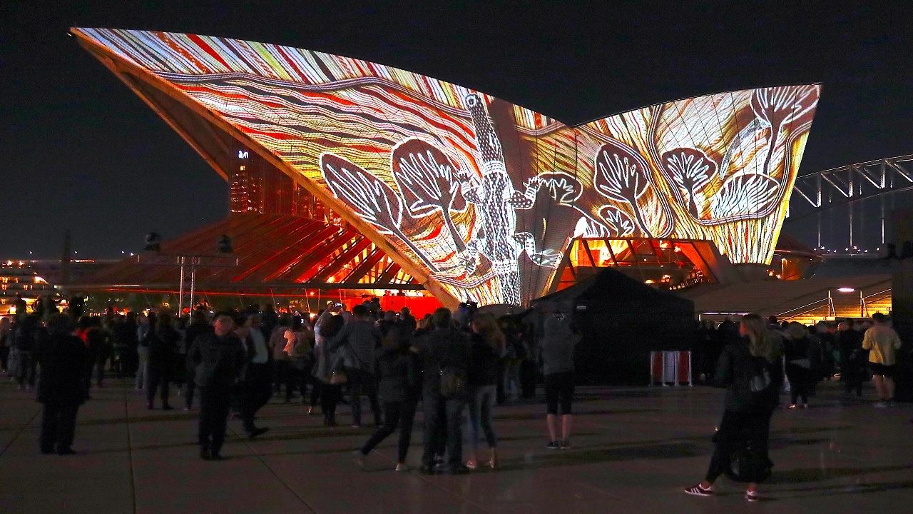 """A crowd watches as Australian Aboriginal paintings by six First Nations artists are projected onto the Sydney Opera House as part of the project """"Badu Gili 2018"""", meaning """"water light"""" in the local Aborigine's Gadigal language, in Sydney, Australia (Image: Reuters)"""