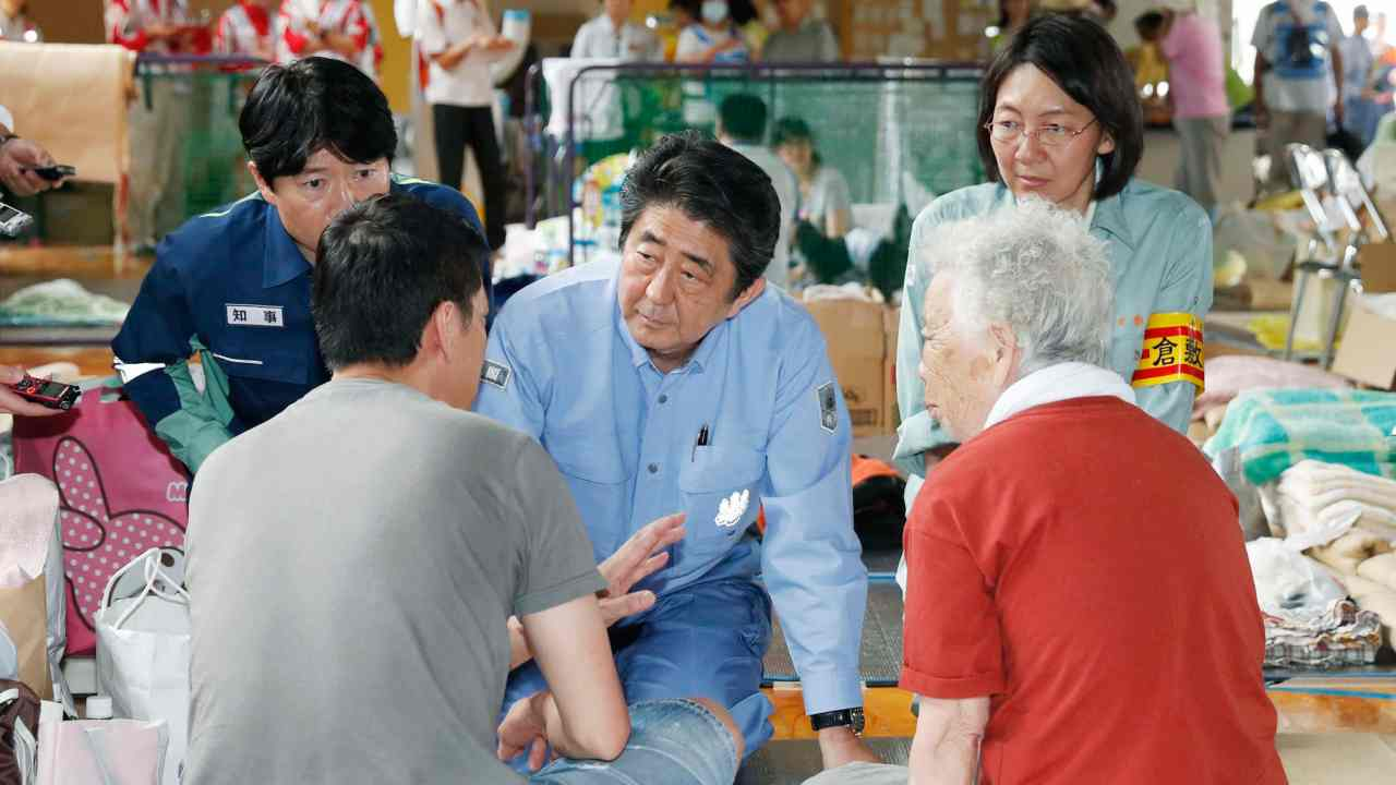 Japanese Prime Minister Shinzo Abe listens to an evacuee during a visit to an evacuation center in Kurashiki, Okayama prefecture, southwestern Japan. Abe visited the hard-hit city where a river broke through an embankment and swept through residential areas. (AP/PTI)