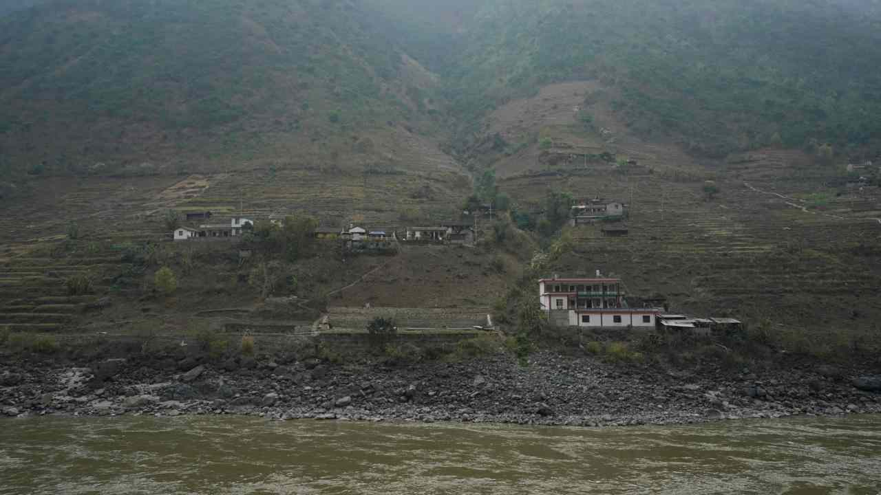 A view of Lazimi village seen from across the river. The nearest bridge over the river is 20 km (12 miles) away from the mountainside village. (Reuters)