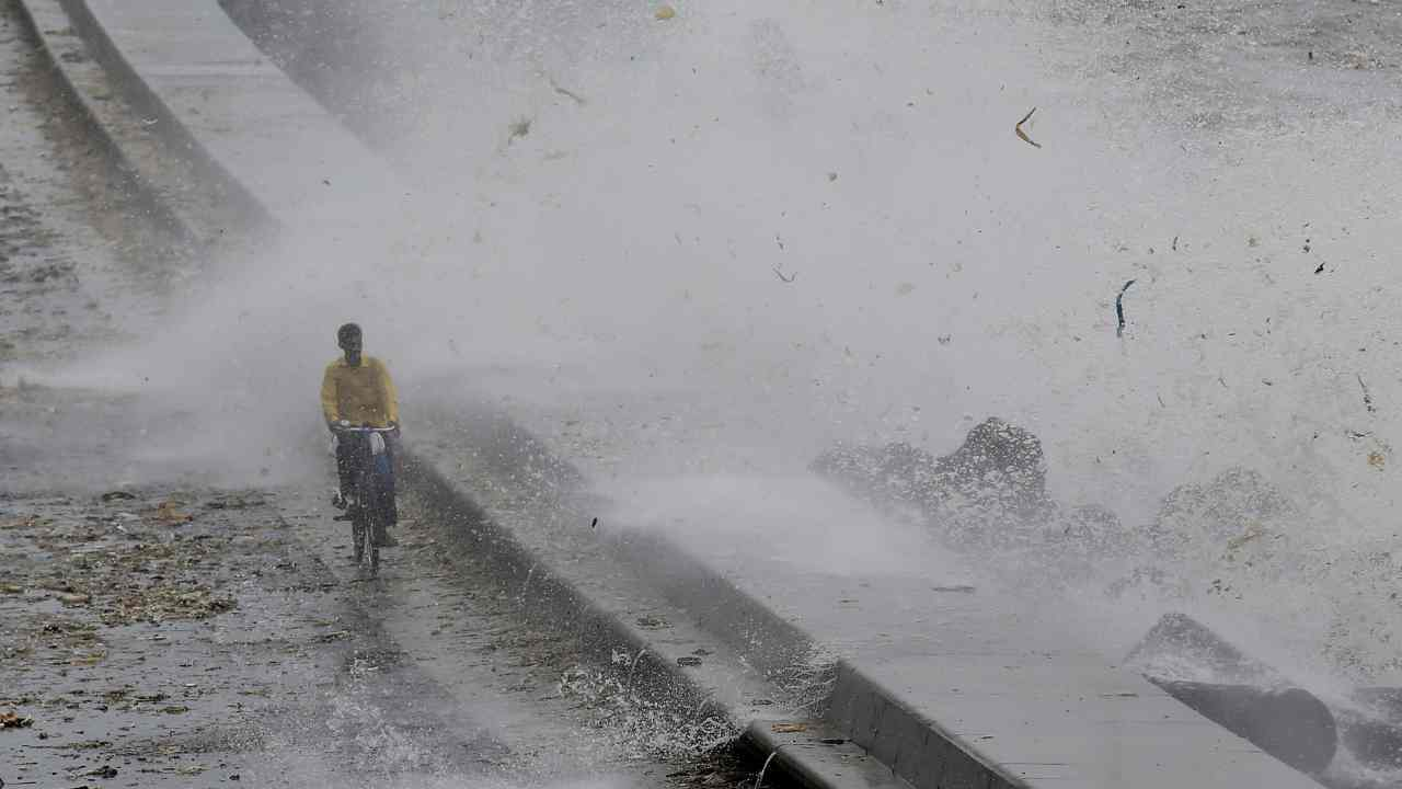 A man rides his bicycle as a wave crashes during high tide at a sea front in Mumbai, India. (Reuters)